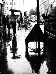 A Rainy Day in Baker Street (cycle.nut66) Tags: road street white black london art film wet monochrome rain sign yard umbrella gate day baker pavement olympus filter rainy figure grainy van grayscale adn blackanndwhite epl1