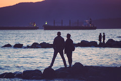 see what you see (Asher Isbrucker) Tags: ocean sea people orange silhouette night vancouver contrast dark boats evening boat twilight couple rocks glow sundown britishcolumbia ships silhouettes romance telephoto englishbay distance westcoast insidevancouver