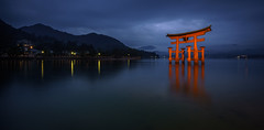 Itsukushima Floating Torii Gate (ErikFromCanada) Tags: old longexposure travel blue sky orange mountain storm mountains reflection water beautiful japan fog night clouds landscape island japanese lights reflecting evening coast gate shrine waterfront pacific cloudy outdoor wide foggy dramatic floating overcast wideangle stormy historic glowing 16mm ultrawide torii landescape itsukushima ultrawideangle smoothwater floatinggate a7r