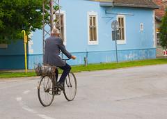 Through town. (mathematikaren) Tags: man bicycle town village serbia balkans easterneurope vojvodina donauschwaben ravnoselo schowe vojvodenia