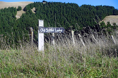 Old School Lodge (Ben Grogan) Tags: blue trees green abandoned field grass sign forest fence low sunny hills tall signpost