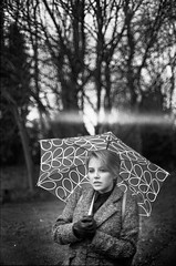 Leah in the cold.. (Charles in Monochrome) Tags: road lighting street uk trees friends portrait england people blackandwhite white black london 120 film monochrome rain contrast vintage reflections mono outfit exposure locals shadows angle outdoor walk candid expressions documentary silhouettes angles objects journey portraiture hp5 medium format a1 experimentation highstreet filmmaking passerby quirky atmospheric composistion filmisnotdead ilfords selfdeveloping
