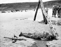 A U.S. soldier lies on the sand of Omaha Beach, killed by German fire on D-Day, as U.S. troops finally capture and secure the beach. The crossed rifles at his feet were put there to form a battle cross, Omaha Beach, Normandy, France, 6 June 1944. [3226x24 (Histolines) Tags: 6 france history feet beach june by soldier fire us sand cross lies battle rifles retro german there his timeline killed were omaha secure form capture normandy dday troops finally 1944 put crossed the vinatage a historyporn histolines 3226x2480 httpifttt25i7xrh