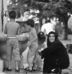 Children, what would they do without mothers (ilmikadim) Tags: boy blackandwhite bw woman playing black girl turkey muslim mother istanbul motherhood turkish turk monocrome chid faountain childiren