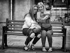 Pretty & The Silly Selfie (Just Ard) Tags: woman girl bench selfie silly people person face street photography candid unposed black white mono monochrome bw blackandwhite noiretblanc biancoenero schwarzundweis zwartwit blancoynegro  justard nikon d750 50mm