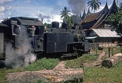 E1064 + Minangkabau houses. Western Sumatra, Indonesia. July 1976 (Brit 70013 fan) Tags: sumatra indonesia railway steam 1976 steamengine padang cupak minangkabau singkarak e1064 indonesianrailways classe10