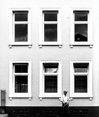 Standing Guard. (Mister G.C.) Tags: blackandwhite bw image streetshot streetphotography candid photograph people unposed monochrome urban town city building architecture windows man male guy sonya6000 sonyalpha mirrorless 20mm pancakelens primelens sel20f28 mistergc schwarzweiss strassenfotografie niedersachsen lowersaxony deutschland europe