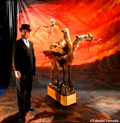 "Immortralizer Dr. Takeshi Yamada poses by his ""Odyssey"" monster, which is a horned five-headed goat monster with bat wings and dragon tail, circled by three dragosn around in the mid air, with a giant hand-painted backdrop of Hell. November 20, 2012 (searabbits23) Tags: ca ny newyork sexy celebrity art hat fashion animal brooklyn asian coneyisland japanese star tv google king artist dragon god vampire famous gothic goth uma ufo pop taxidermy vogue cnn tuxedo bikini tophat unitednations playboy entertainer oddities genius mermaid amc mardigras salvadordali performer unicorn billclinton billgates aol vangogh curiosities sideshow jeffkoons globalwarming mart magician takashimurakami pablopicasso steampunk losangels damienhirst cryptozoology freakshow leonardodavinci realityshow seara immortalized takeshiyamada roguetaxidermy searabbit barrackobama ladygaga climategate"