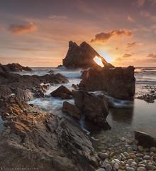 Sunrise through the hole (Andrew Paul Watson) Tags: light sea sunrise scotland hole tide scottish fujifilm through geology moray firth xt1 throughthehole bowfiddlerock