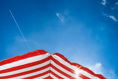 Red White and Blue (Roberto Spagnoli) Tags: summer sky color beach clouds wake nuvole estate geometry cielo spiaggia aereo redwhiteblue scia beachumbrella ombrellone