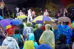 Wild Tchoupitoulas in the Rain (spinadelic) Tags: new music wet rain weather festival orleans colorful bass stage south crowd band vivid player lsu april nola vest tradition mic jazzfest umbrellas outfits nawlins stevespencer outlandish 2016 wildtchoupitoulas heritagestage