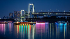Rainbow Bridge (adrianchandler.com) Tags: city nightphotography bridge blue urban reflection water japan architecture night river asian boats japanese lights tokyo boat asia neon cityscape exterior nightscape outdoor hour bluehour bankside