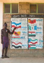 Hamer tribe teenager in a school in front of a painted wall with the regions flags of ethiopa, Omo valley, Turmi, Ethiopia (Eric Lafforgue) Tags: poverty africa school people color childhood vertical painting outdoors photography necklace education mural day african cellular tribal flags mobilephone teenager bead omovalley schools ethiopia tribe development hamar oneperson telecom telecommunication developingcountry hamer hornofafrica ethiopian riftvalley wallpaintings eastafrica abyssinia realpeople teenageboy beadednecklace lookingatcamera ruralscene buildingexterior fulllenght turmi africanethnicity 1people indigenousculture beadednecklaces oneteenageboyonly ethiopianethnicity ethio161856