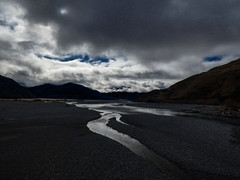 Greywacke Gravel (Steve Taylor (Photography)) Tags: blue newzealand cloud white black cold water silhouette stone river landscape spring bed perspective nz southisland southernalps gravel greywacke