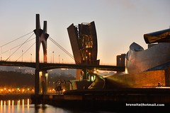 The museum and the morning (brunaita) Tags: trip viaje bridge light espaa tourism monument architecture backlight contrast contraluz puente dawn luces licht spain arquitectura colours monumento tranquility colores bilbao amanecer contraste architektur brcke turismo sonnenaufgang euskadi spanien reise farben guggenheimmuseum denkmal pasvasco tranquilidad ra ruhe explored museoguggenheim gegenlichtaufnahme inexplore nikonv2 nikon1nikkor30110vr