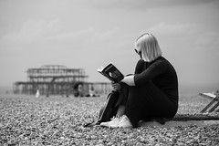 The old fashioned way of entertainment (judethedude73) Tags: life street sea summer england west beach photography reading book coast pier brighton candid pebbles