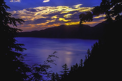 Sunrise over Crater Lake (woodchuckiam) Tags: trees lake reflection colors clouds oregon sunrise landscape scenic silhouettes caldera vegetation craterlake rays craterlakenationalpark woodchuckiam