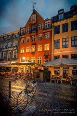 Bicycle in Nyhavn in the Morning (Jacob Surland) Tags: city lines bicycle clouds copenhagen denmark nyhavn harbor cafe closed cityscape fineart cobblestones oldhouse newport dk lamps bluehour ambience hdr highdynamicrange oldbuilding warmlight fineartphotography citybynight capitalregionofdenmark caughtinpixels jacobsurland