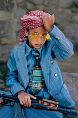 Child Army Steve McCurry (Larry Oxendine) Tags: blue boy red portrait sunglasses yellow rock vertical stone outside soldier outdoors gold glasses gun sitting exterior child hand head buttons stripes headscarf rifle young knife 1999 suit sit yemen walls patch striped nationalgeographic headdress april2000 hajja hajjah yemen10042