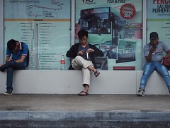 A little snack (appropos) Tags: street people waiting sitting busstop sit seated snacking