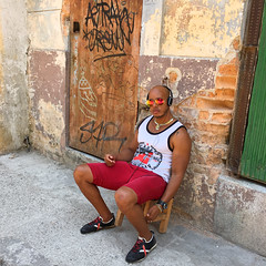 Cuban man listening to the music (piginka) Tags: street old city people music male men wall architecture outdoors photography town sitting havana cuba young relaxation obsolete capitalcity urbanscene humanface colorimage buildingexterior africandescent cubanculture builtstructure