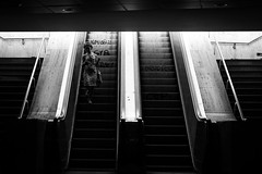 Consumed by Limbo [explored] (Thomas Demeulemeester) Tags: summer bw streetart byn stairs bag subway women university day phone graffity connected escalators ef50mmf18ii backlighting urbanlandscape handrails bucarest blackwandwhite downlights urbancity canon600d