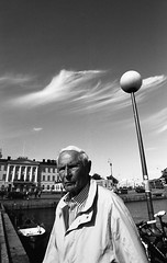Portrait of a man with clouds (__ _) Tags: blackandwhite man clouds finland helsinki scenery skies candid streetphotography elderly homecooked socialdocumentary pushprocess panf selfdeveloped streetportraiture filmisnotdead
