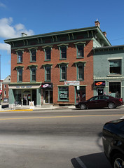 Terry Building  Mount Vernon, Ohio (Pythaglio) Tags: warren building terry structure historic commercial mount vernon ohio mtvernon knox county threestory brick 11 windows hoodmolds storefronts cornice brackets frieze chimneys signs ca1832 kno32814 sidewalk street cars slope hill sky blue clouds