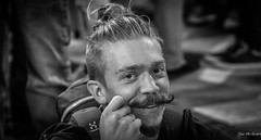 2016 - Baltic Cruise - St. Petersburg - Teasing the Stash (Ted's photos - For Me & You) Tags: 2016 cropped tedmcgrath tedsphotos vignetting russia ussr thechurchofthesavioronspilledblood male man moustache bw blackwhite backpack teeth dents face portrait