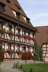 Nuremberg, Germany - Aug 23, 2016: Inside view of the Kaiserburg, Medieval Castle in Nuremberg, Germany. In World War II, the castle was damaged in 1944-45, with only the Roman double chapel and the Sinwell Tower remaining entirely intact. (Alma de Angel) Tags: bavaria burg castle emperor franconia germany kaiser medieval nuremberg tower bricks kaiserburg summer travel medievalarchitecture middleages tourist architecture tourism medievalstreet steeple cityscape square town landmark culturalheritage clouds sightseeing historicmonuments castleroad sky europe bluesky landscape sinwelltower inside spring flowers
