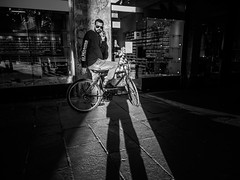 ... sharing glances!!! (Fede Falces ( ...... )) Tags: barcelona urban blackandwhite bw man me girl look sunglasses bike contrast myself eyecontact shadows noiretblanc candid young olympus sp sharing streetphoto f28 myshadow raval selfie glances shadowselfie
