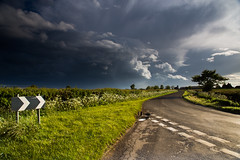 Stormy road (andyk11) Tags: road uk sun sunlight storm black tree rain weather sign clouds dark spectacular post dramatic stormy hedge sunlit wiltshire mighty chevron thunder pothole roadtohell brinkworth