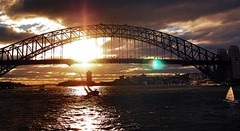 the sailor and the bridge (mugley) Tags: city travel sunset sky urban sun water skyline architecture clouds digital buildings boats iso200 waves sailing cityscape zoom sydney silhouettes kitlens australia olympus nsw flare newsouthwales cropped lunapark ghosts f56 omd urbanlandscape sydneyharbourbridge milsonspoint skyscapers portjackson 14mm cloudage 1442 thecoathanger em5 11250s stoppeddown mirrorless zoomedout mahonspoint micro43 microfourthirds mzuiko1442mmf3556iir olympusem5