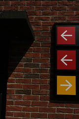DSC03450 (The Man-Machine) Tags: shadow red signs sign yellow office squares brickwall arrows arrow