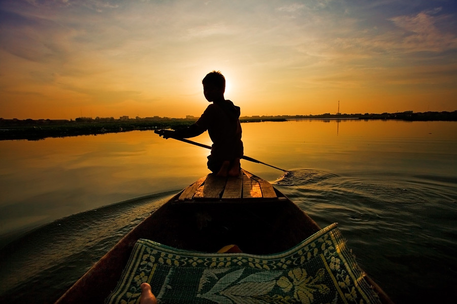 Young-Cambodian-boy-paddling-at-sunset