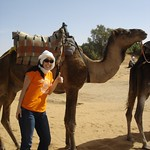 A student poses with a camel in a desert.