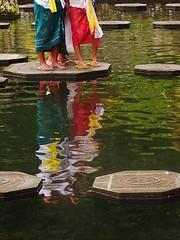 three on a stepping stone (SM Tham) Tags: ladies bali water gardens reflections outdoors island pond women asia colours steppingstones slippers balinese waterpalace sarongs karangasem tirtagangga amlapura sashes laceblouses gardenstosee