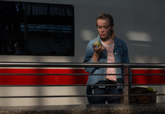 Moments (Georgie Pauwels) Tags: street apple public station train women waiting eating candid streetphotography railway olympus moment