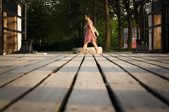 grounding (jaumescar) Tags: street city red urban music woman girl lines composition canon walking lens photography prime movement alone dof dress low go symmetry listening step pow leading