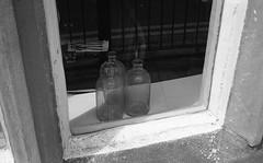 Three Bottles (Man with Red Eyes) Tags: 3 window monochrome analog three blackwhite bottles rangefinder lancashire lancaster m6 leicam6 adox silverhalide v850 td201 silvermax anchelltroop 40mmf14voigtlandersc a3minsb3mins continuousagitation
