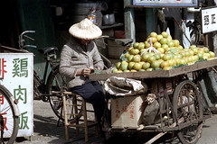 32-622 (ndpa / s. lundeen, archivist) Tags: nick dewolf nickdewolf 32 reel32 color photographbynickdewolf 1970s 1972 fall film 35mm winter republicofchina taiwan taiwanese china chinese city citylife streetlife streetphotography candid people vendor fruit produce streetvendor hat conicalhat traditionalhat cart wagon street cigarette smoker smoking citrus bike bicycle