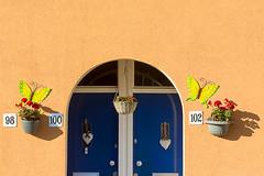 Two doors, two plants .. . (Jan van der Wolf) Tags: map1578v doors door blue blauw scheveningen muur wall planten plants shadow schaduw dissymmetry house building huis gebouw two 98 100 102 brievenbus postbox