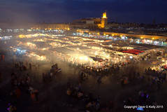 Jemaa el-Fna (Dave G Kelly) Tags: road city sky people motion shop horizontal retail architecture speed shopping walking square outdoors photography alley day cityscape market dusk citylife mosque illuminated business morocco medina marrakesh consumerism crowded streetmarket buying marketstall jemaaelfna blurredmotion cloudsky traveldestinations buildingexterior koutoubiamosque largegroupofpeople unrecognisableperson colourimage elevatedview moroccanculture builtstructure djemmaelfnasquare incidentalpeople smokephysicalstructure