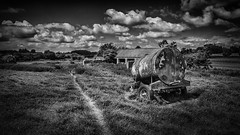 Rusty Water Bowser (aj_nicolson) Tags: sky blackandwhite water field grass clouds barn rural landscape bowser noiretblanc outdoor path farm appicoftheweek