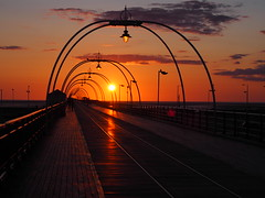 Sunset walk along the Pier (flamesworddragon) Tags: southport sunset pier perspective lighting sun clouds orange