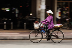 Vietnam. Saigon. Going somewhere (TikoTak) Tags: woman hat women asia vietnam asie panning bicyclette saigon conical cycliste fil spanning file