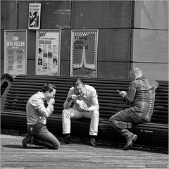 Sacred lunch (John Riper) Tags: street friends summer bw white man black netherlands monochrome canon john square lunch photography mono rotterdam hands zwartwit candid posters l colleagues knees kneeling snacking doelen 6d 24105 straatfotografie riper schouburgplein johnriper photingo