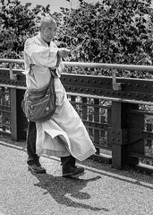 Please Take One (melmark44) Tags: backlight highline monk robe streetphotography street bw blackandwhite nyc newyorkcity shadow hellskitchen fake buddhistmonk beggar westside candid