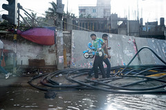 The electric serpentine and men fighting over a tricycle (AvikBangalee) Tags: water bike outdoor tricycle streetphotography sidewalk vehicle dhaka footpath powercable avikbangalee peopleandliving swearage