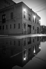 Twilight Reflections (tim.perdue) Tags: street city blue windows columbus ohio urban bw white black building water monochrome rain sign corner reflections way puddle lights one evening twilight alley downtown doors olympus wires hour intersection omd athenaeum em10